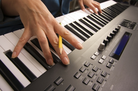 Woman's Beautiful Hands hold Pencil on Digital Piano Keys